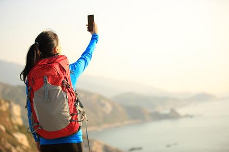 mochila de viaje: senderismo mujer toma la foto con el teléfono en la cima de la montaña