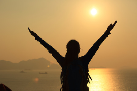 trekker: cheering hiking woman open arms to the sunrise stand at seaside mountain Stock Photo