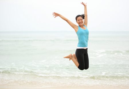 chinese women: Happy woman jumping on the beach. summer holidays