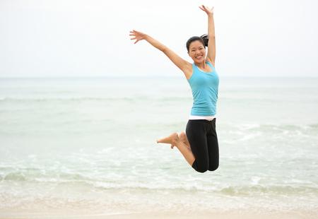 niñas chinas: Mujer feliz que salta en la playa. vacaciones de verano