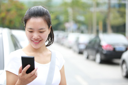 one people: young asian woman use her cellphone walking at parking lot Stock Photo