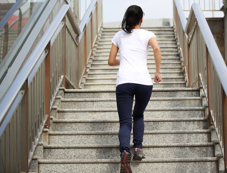 woman stairs: woman running on stairs Stock Photo