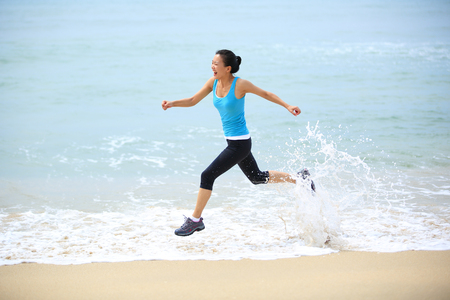the flood tide: sporty lifestyle asian woman running at beach with spraying sea water