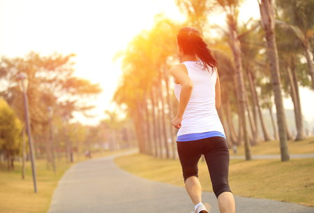 asian trees: Runner athlete running at tropical park. woman fitness sunrise jogging workout wellness concept. Stock Photo