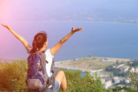 ser humano: animando jóvenes Caminante de la mujer los brazos abiertos en pico de la montaña junto al mar Foto de archivo