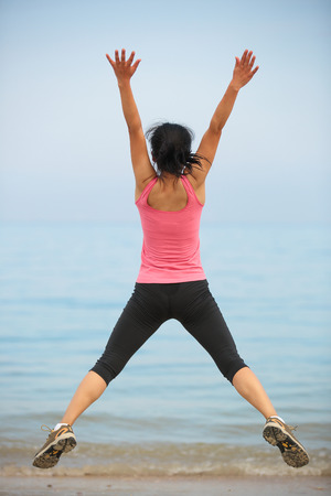 outdoor exercise: happy woman jumping at seaside beach in summer holidays