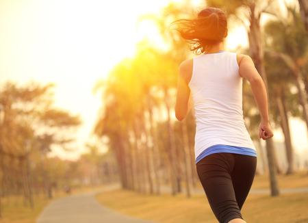 corriendo: mujer corriendo en el parque tropical Foto de archivo