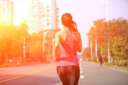mujer alegre: Mujer deportiva sana que se ejecuta en la ciudad de la calle de asfalto