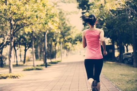 健身: 健康的生活方式女人在城市公園的路面上運行