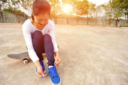 young woman sit on skateboard try new shoes