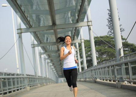 Footbridge: beautiful healthy lifestyle young asian woman running at modern city footbridge