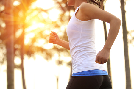 Runner athlete running at tropical park. woman fitness sunrise jogging workout wellness concept. Banque d'images