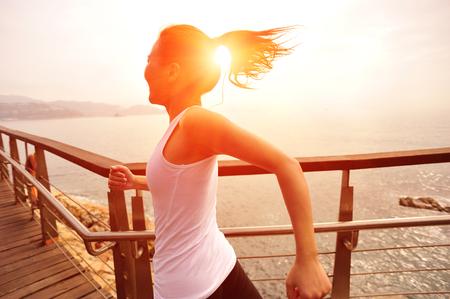 ser humano: Mujer deportes de estilo de vida saludable que se ejecuta en la playa pasarela de madera Foto de archivo