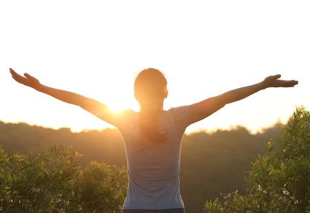 arm raised: cheering woman open arms at sunrise mountain peak