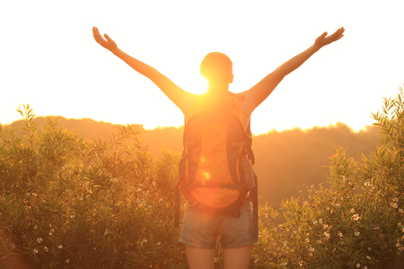 thankful woman hiker open arms to the sunrise stand at mountain peak Stock Photo