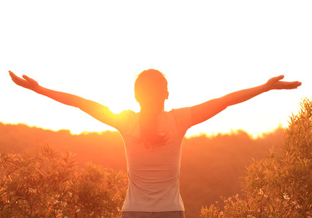 sunup: thankful woman open arms to the sunrise stand top of mountain