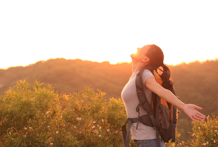 red mountain open space: thankful woman hiker open arms to the sunrise stand at mountain peak Stock Photo