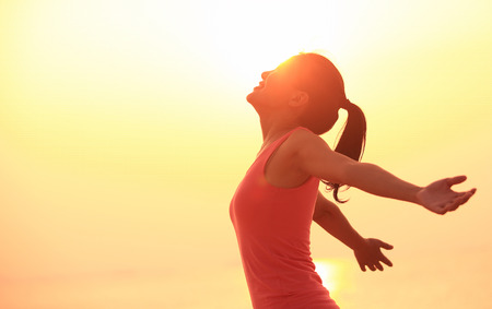 cheer: young fitness woman open arms under the sunrise at sea Stock Photo