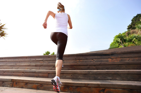 woman stairs: healthy lifestyle sports woman running up on wooden stairs