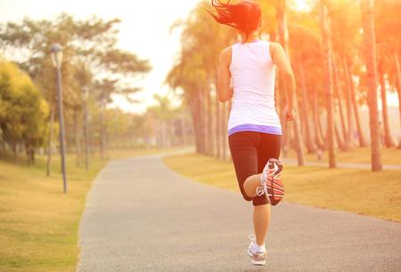 atleta corriendo: Runner atleta que corre en el parque tropical. mujer de la aptitud que activa la salida del sol entrenamiento concepto de bienestar. Foto de archivo