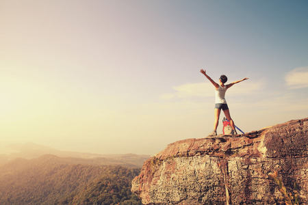 cheering woman hiker open arms at mountain peak Stockfoto