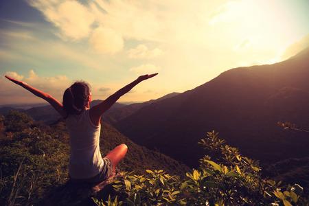 prática de ioga mulher no pico da montanha