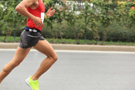 Marathon runner running on city road Stockfoto