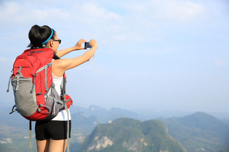taking photo: young woman backpacker taking photo with camera on mountain peak