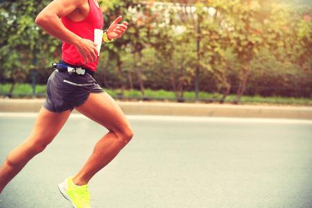 run: Marathon runner running on city road Stock Photo