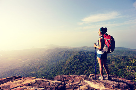 backpack: young woman backpacker enjoy the view at seaside mountain peak
