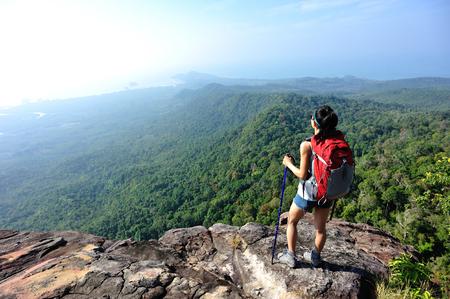 young woman backpacker climbing to mountain peak Stock Photo