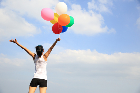 young woman cheering on mountain peak with colorful balloons