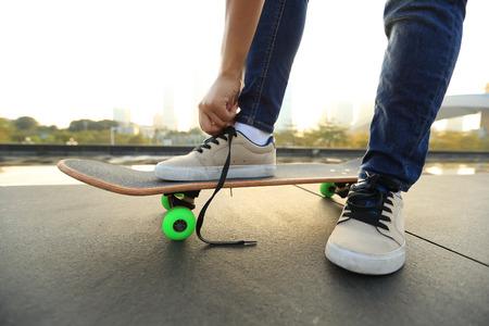 shoelace: skateboarder tying shoelace on city