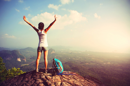 cheering woman hiker open arms at mountain peak Stockfoto