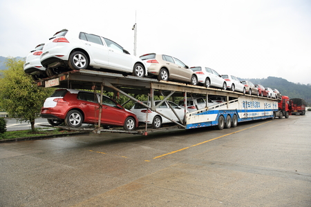 hauler: Big rig semi-truck car hauler with new cars on road. Editorial