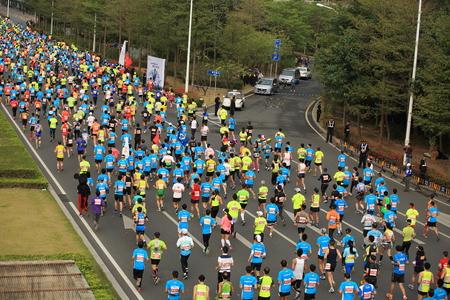 competitividad: Shenzhen, China - DICIEMBRE 7: corredores de marat�n no identificados en la calle en el marat�n internacional de Shenzhen 7 DE DICIEMBRE DE, 2014 en Shenzhen, China