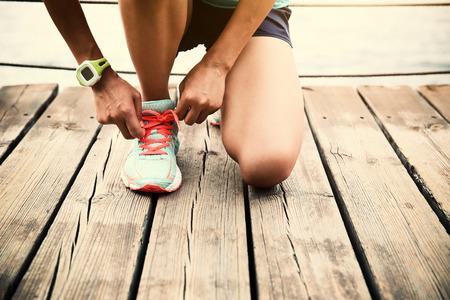 piernas mujer: deportes corredor de la mujer atar cordones de los zapatos en la playa pasarela de madera Foto de archivo
