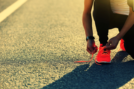 woman run: young sports woman runner tying shoelace on city road