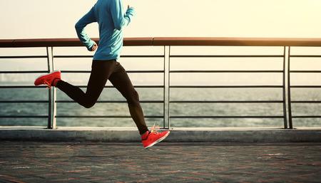 海辺でジョギング フィットネスの若い女性 写真素材