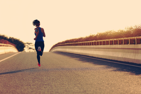 people shadow: young fitness woman runner running on sunrise road Stock Photo