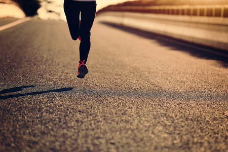 legging: young sports woman runner running on city road Stock Photo