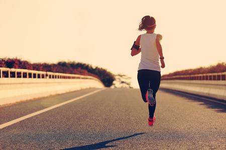 legging: young fitness woman runner running on sunrise road Stock Photo