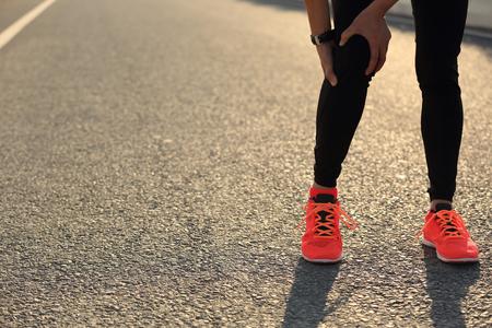 dolor de rodilla: Corredor de la mujer sosteniendo su pierna lesionada en el camino Foto de archivo