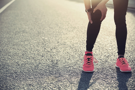 twitch: woman runner hold her injured leg on road