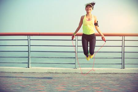 해변에서 밧줄을 점프하는 젊은 피트 니스 여자 스톡 콘텐츠