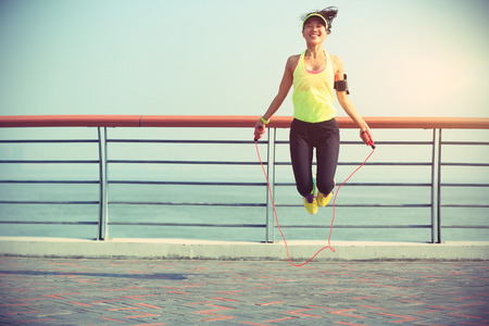 young fitness woman jumping rope at seaside Foto de archivo