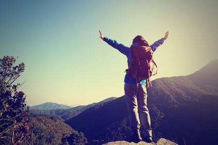 asian success: successful woman hiker open arms on sunrise mountain peak