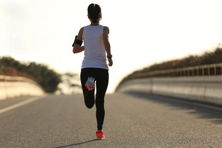 marathon runner: young fitness woman runner running on sunrise road Stock Photo