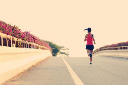 escucha activa: joven mujer de fitness corredor corriente en la carretera Foto de archivo