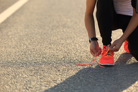 woman listening to music: young sports woman runner tying shoelace on city road